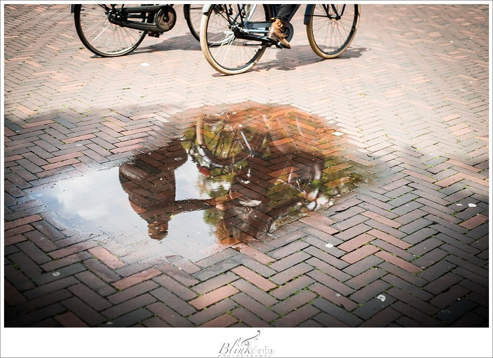Reflection of cyclers in puddle in Zuidpoort, located in Delft.