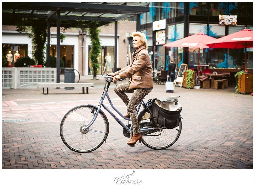 Fashionable woman cycles with style through the streets of Delft.