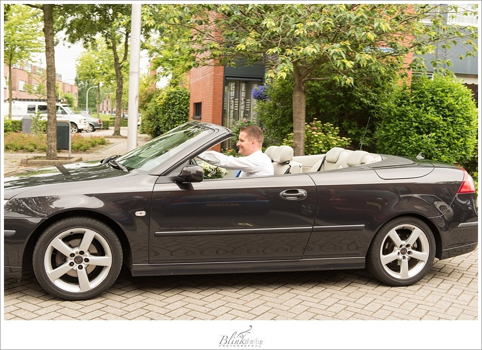 Groom arrives in convertible for wedding in Delft.