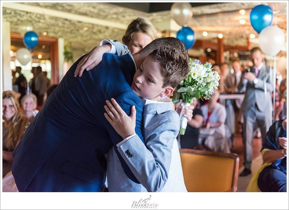 Groom hugs his son during wedding ceremony.