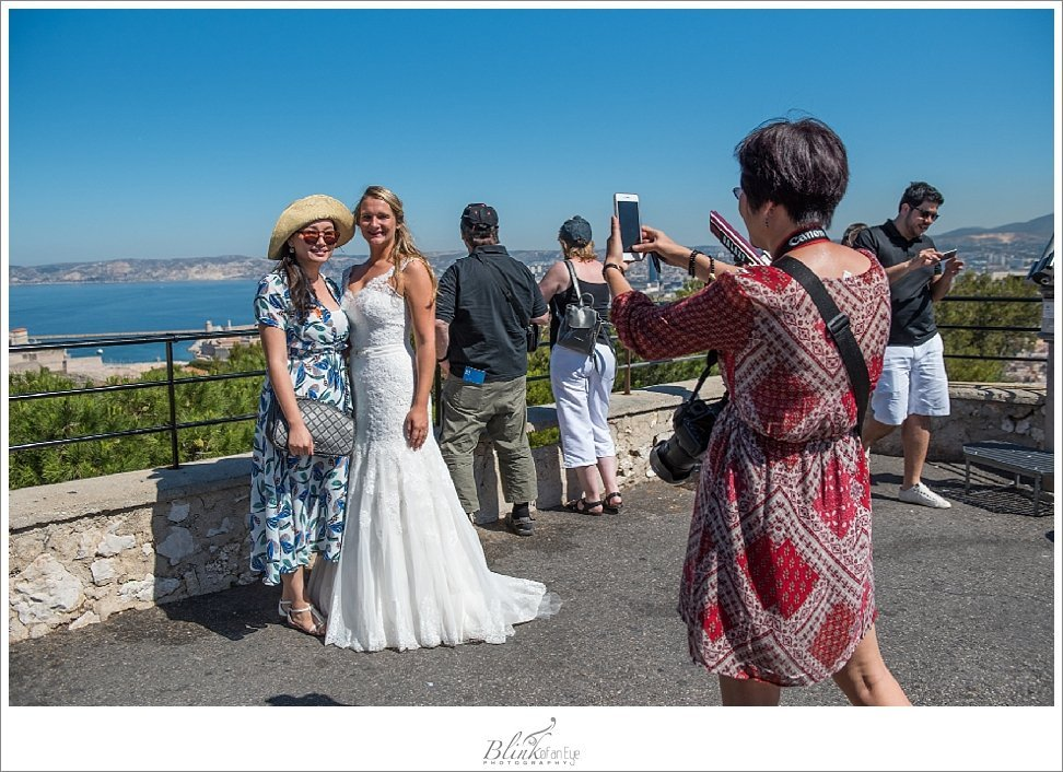 Tourists photograph bride in Marseille, France.