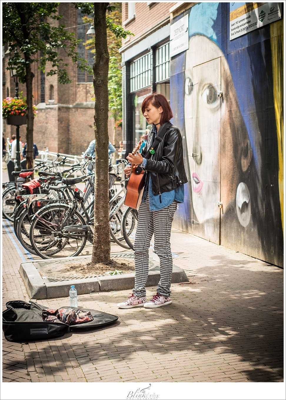 Street artist sings in Delft with The Girl With a Pearl Earring as a backdrop.