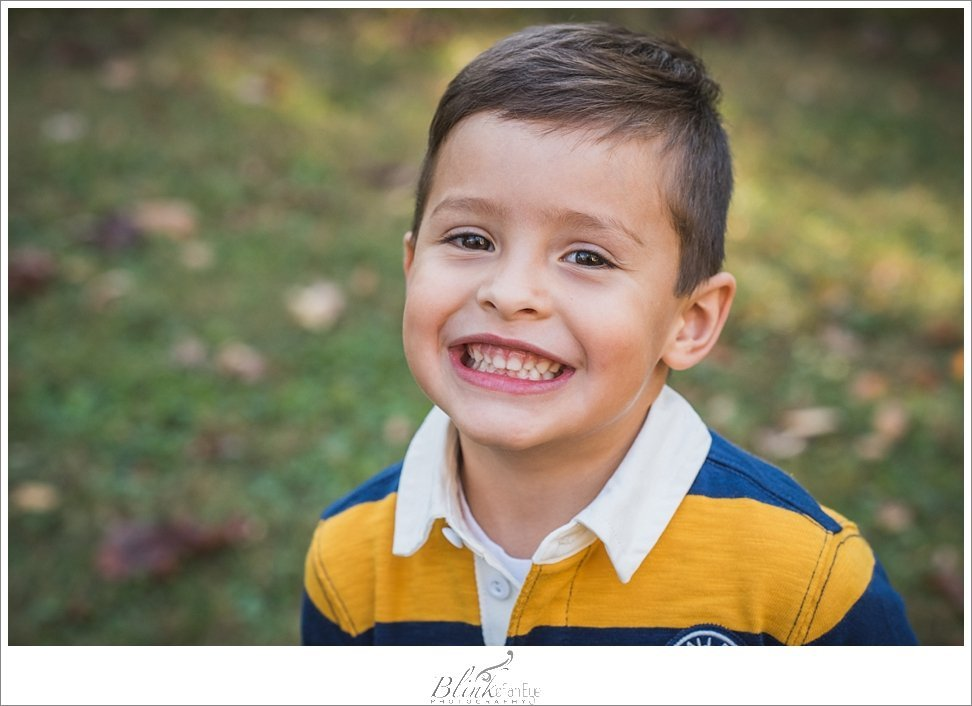Handsome boy flashes a big smile for Greesnboro portrait photographer.