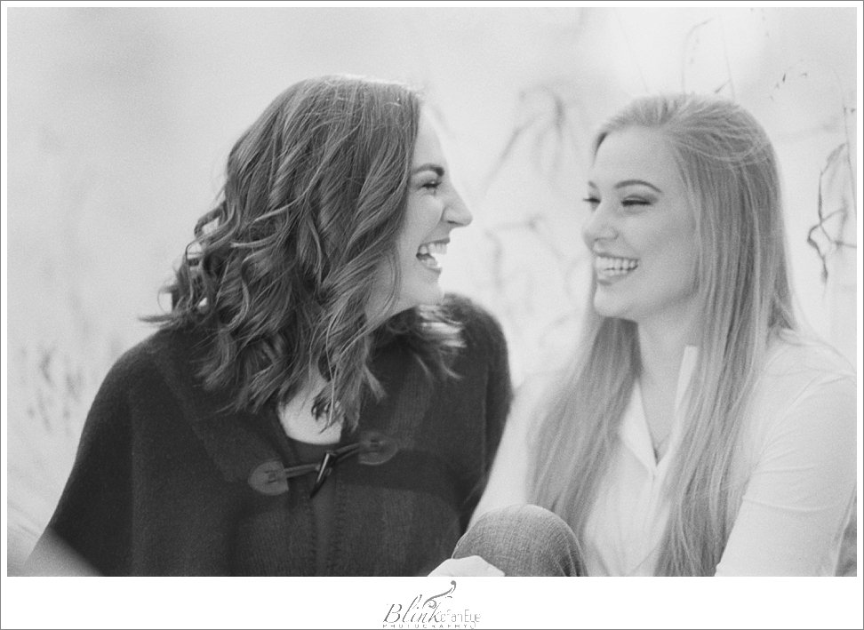 Sisters laughing in black and white film photograph,