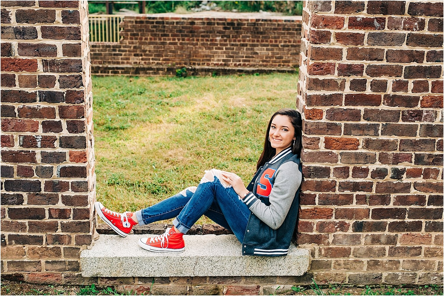 Awesome letter jacket and red high top shoes in this senior portrait.