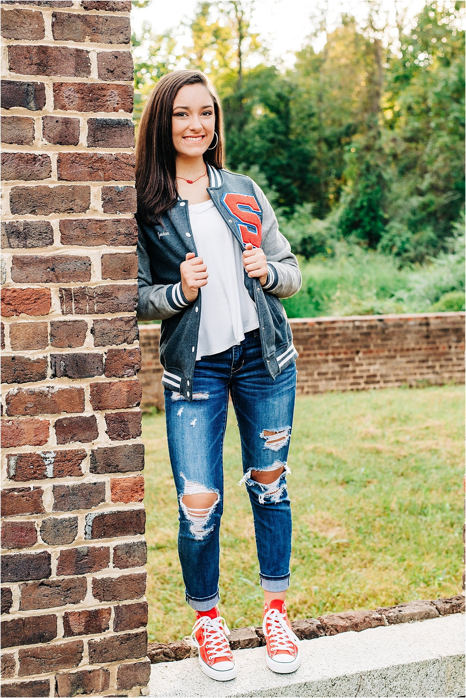 Senior volleyball star poses in letter jacket and red high tops!