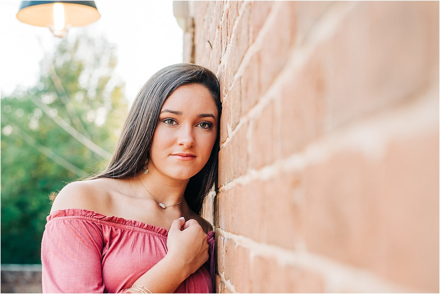 Pensive senior portrait against wall in Burlington, NC.